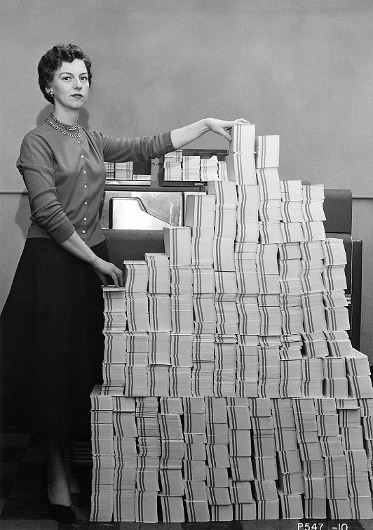 Programmer standing beside punched cards This stack of 62,500 punched cards — 5 MB worth — held the control program for the giant SAGE military computer network. 1955 ca. © MITRE Corporation