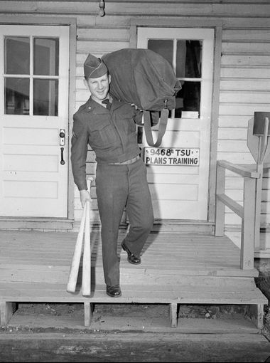 Whitey Ford, 24, a southpaw who helped pitch the New York Yankees to the 1950 world championship, carries a duffel bag and bats as he leaves the barracks at Fort Monmouth, N.J., Nov. 19, 1952.  AP