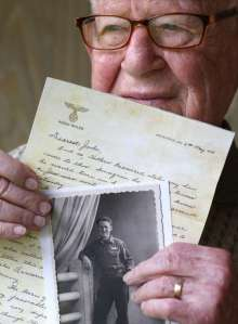 © Charles Trainor Jr./Miami Herald/TNS Danny Jacobson holds a photo copy of a letter written on Adolf Hitler's stationary with a photo of himself in uniform in World War II. He found the stationery in an abandoned apartment in Munich.