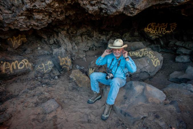Ike Eastvold, sitting in a graffiti-marred cave near the head of Boca Negra Arroyo at the Petroglyph National Monument, holds his hands to his ears to better hear the wind and the wildlife on the monument grounds. Eastvold, a longtime supporter of the monument on the Albuquerque's West Side, discovered the graffiti, litter and downed fencing while walking last week. (Roberto E. Rosales/Albuquerque Journal)